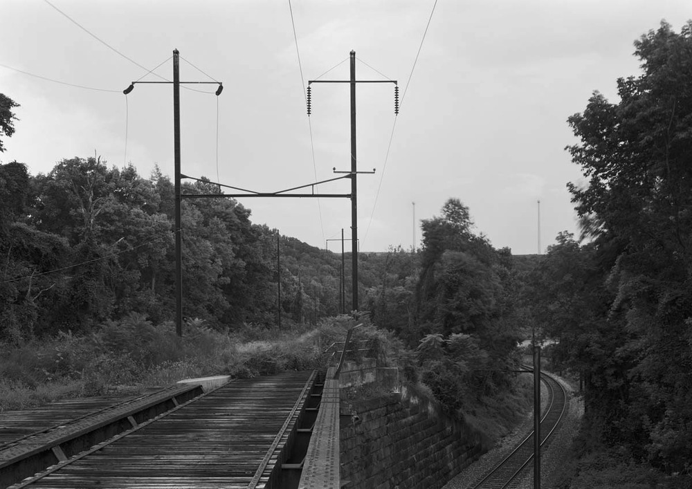 A&S jump-over bridge looking east at Port/ Cres interlocking. The track below is the westward main track of the Columbia and Port Deposit branch. Around the bend below is Cres, where this track meets with the eastward main and narrows to one track. Note the transmission poles that are still used to support Amtrak's feeder line from Safe Harbor to Royalton preserving for now some of the visual characteristics of the original PRR infrastructure.
