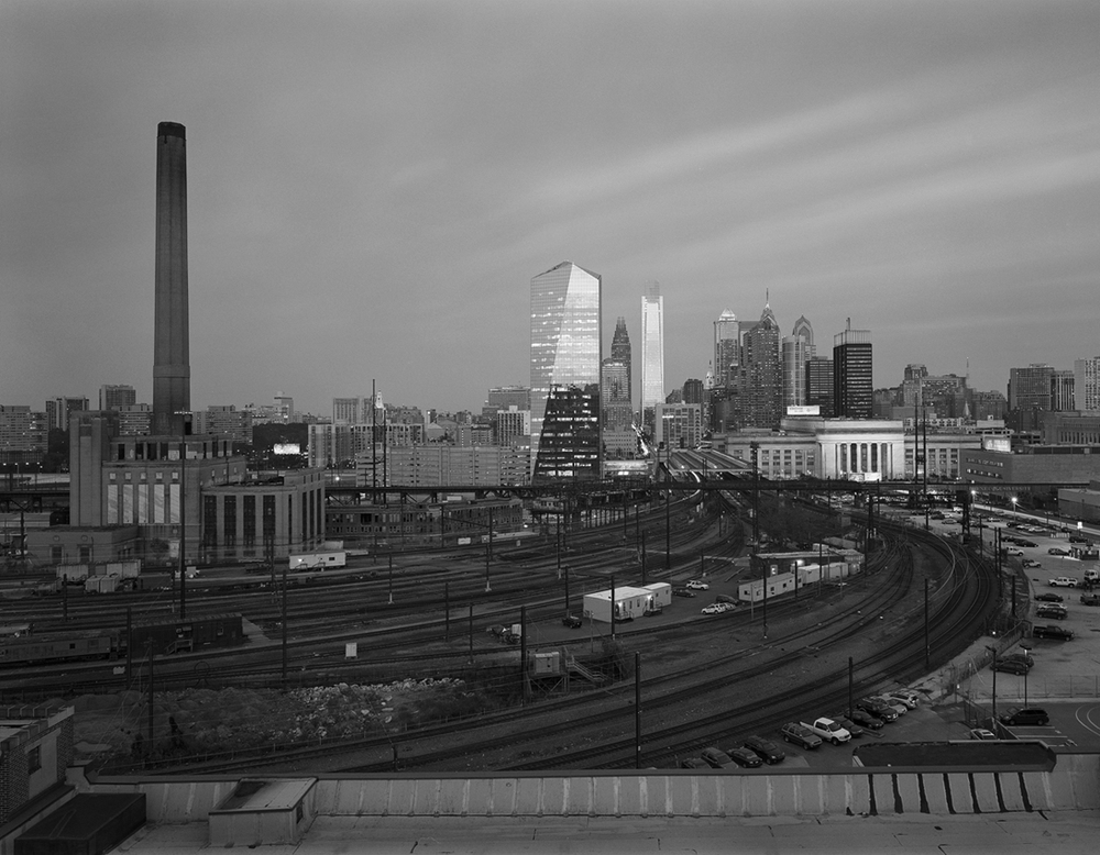 This view reveals a perspective of the finished Philadelphia Improvements showing how the Pennsylvania Railroad's efforts continue to serve the traveling public today. Seventy six years after the 30th Street Station complex opened, the matching steam plant and neighboring Pullman commissary would be demolished to make way for a parking lot and maintenance facility for Amtrak. Just two weeks after this photo the landscape would change yet again with the removal of the iconic steam plant, known affectionately to Drexel University students as the Drexel Shaft.