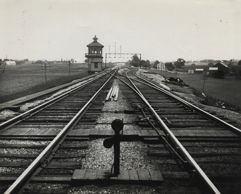 The western end of the Downingtown & Lancaster Branch joined the PRR Main Line just east of the Conestoga River bridge. This undated view of ES tower with its classic wood frame structure looks east on the main line where it collapses from four to two tracks to cross the Conestoga. Left and behind the tower you can see the diverging route of the D&L. Image is from the collection of the  Lancaster History Archive