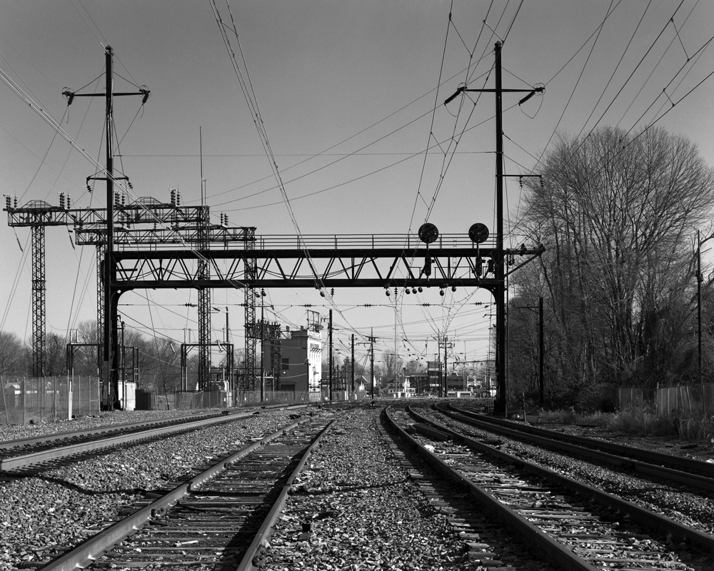 View looking east at the western limits of the Paoli interlocking plant. Number 2 and 3 track mains (center tracks) are basically stub end sidings here used occasionaly for track and maintenance equipment. The surviving infrastructure of the electrification reflects various generations of expansion including the massive singnal bridge, tubular trolley poles and the sub-station. This would have been some of the western most electrified trackage until the 1938 expansion to Harrisburg. Note: This photograph was taken with Amtrak permission under watchman protection, the author does not condone any type of trespassing on railroad or private property.