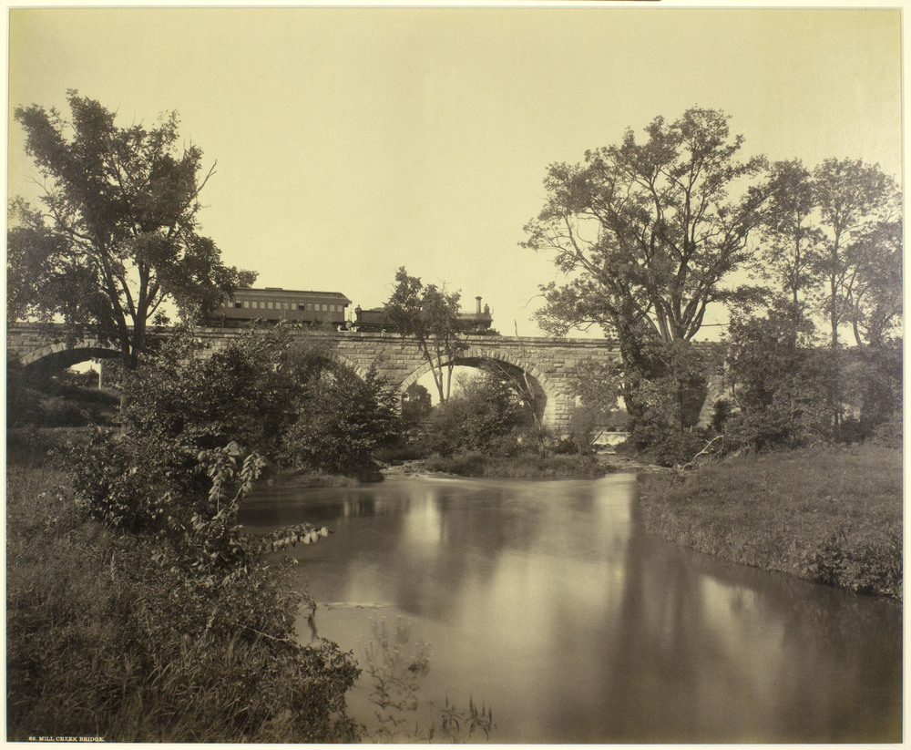 Plate 68: Mill Creek Bridge. Facing the southern facade of a virtually brand new bridge spanning Mill Creek, photographer William H. Rau frames the special photography train staged on the bridge. Very little has changed here with the exception of the concrete reinforcement and catenary towers as seen by the inset photo below taken in 2013. William H Rau image collection of American Premier Underwriters, Inc.
