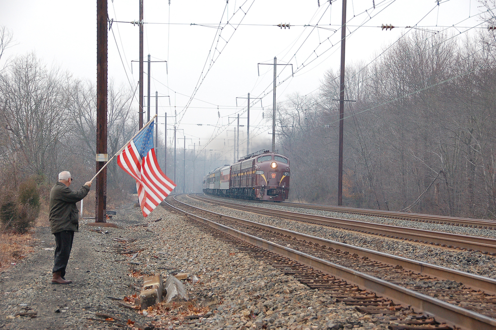 Passing through Chase Maryland, on Amtrak's Northeast Corridor, the Liberty Limited, powered by Bennett Levin's 2 E8 locomotives pulling 19 private cars carrying military personnel wounded in the service of our country, is enroute from Washington, D.C. to the Army-Navy football game in Philadelphia, PA. Waving a flag that had flown over our nation's capitol, retired Army Reserve Colonel Lex Bishop lets the military personnel aboard the special train know that their service & sacrifice is appreciated. Photography by Don Kalkman Jr.