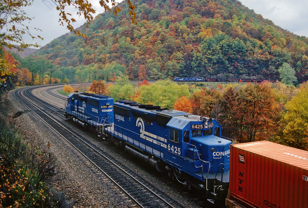 Two Conrail trains part ways at iconic Horseshoe Curve west of Altoona, Pennsylvania on the former Pennsylvania Railroad mainline over the Alleghenies, October 21, 1988. Image courtesy of Mike Danneman