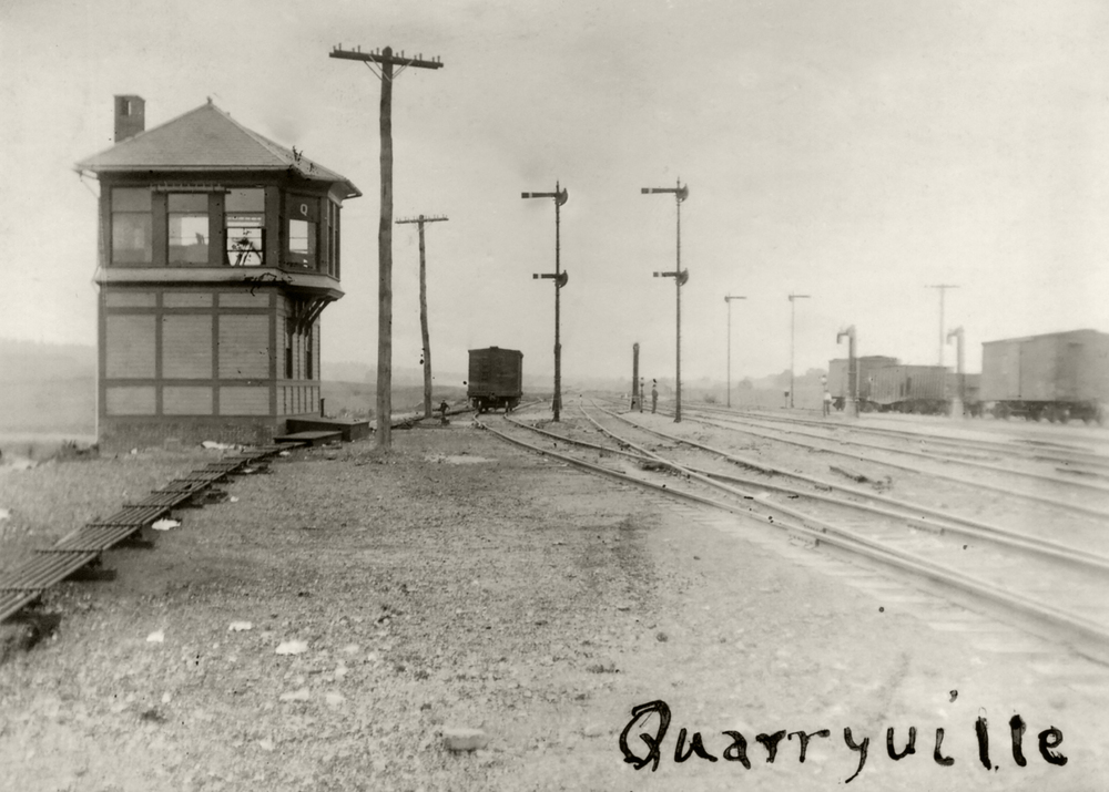 "This 1906 view shows the wood frame tower at Quarryville (Milepost 10.8), the first interlocking tower west of Parkesburg. ""Q"" had control over the two main tracks and four additional sidings to manage helper movements assisting trains to Mars Hill Summit. Additionally four water columns were available to top off steam locomotive tenders on their journey east or west. Image collection of William L. Seigford"