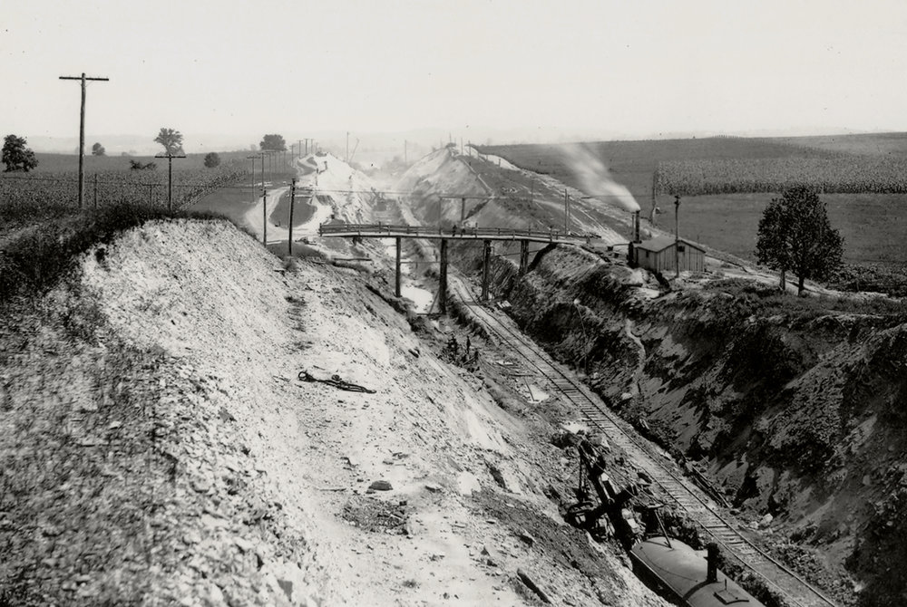 This cut excavated on the Manor Township section of the Atglen and Susquehanna illustrates the massive scope of ongoing work. The temporary narrow gauge track used to haul some of the 1.3 million cubic yards of debris is evident in the cut complete with a steam shovel at lower right, one of the key pieces of equipment for such work. Harry P. Stoner photograph, Columbia Historic Preservation Society