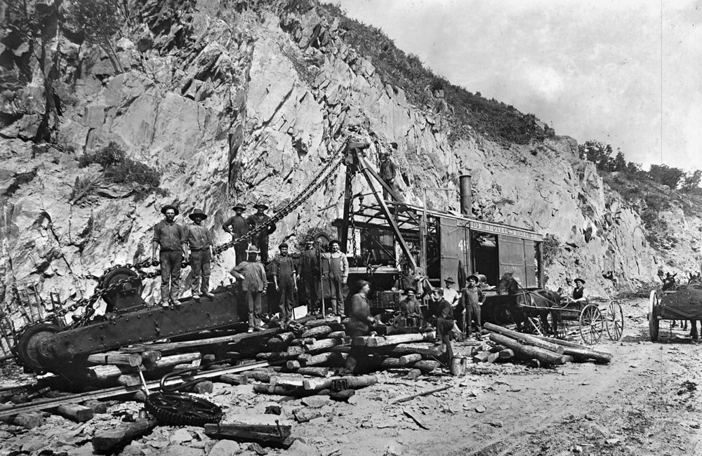An excavation crew pauses with a rail mounted steam shovel that appears to be down for repairs. Steam shovels and air powered drills were initially utilized to excavate the right of way in Manor township as well as the deep cuts along the line to the east. Kline Collection, Railroad Museum of Pennsylvania, PMHC