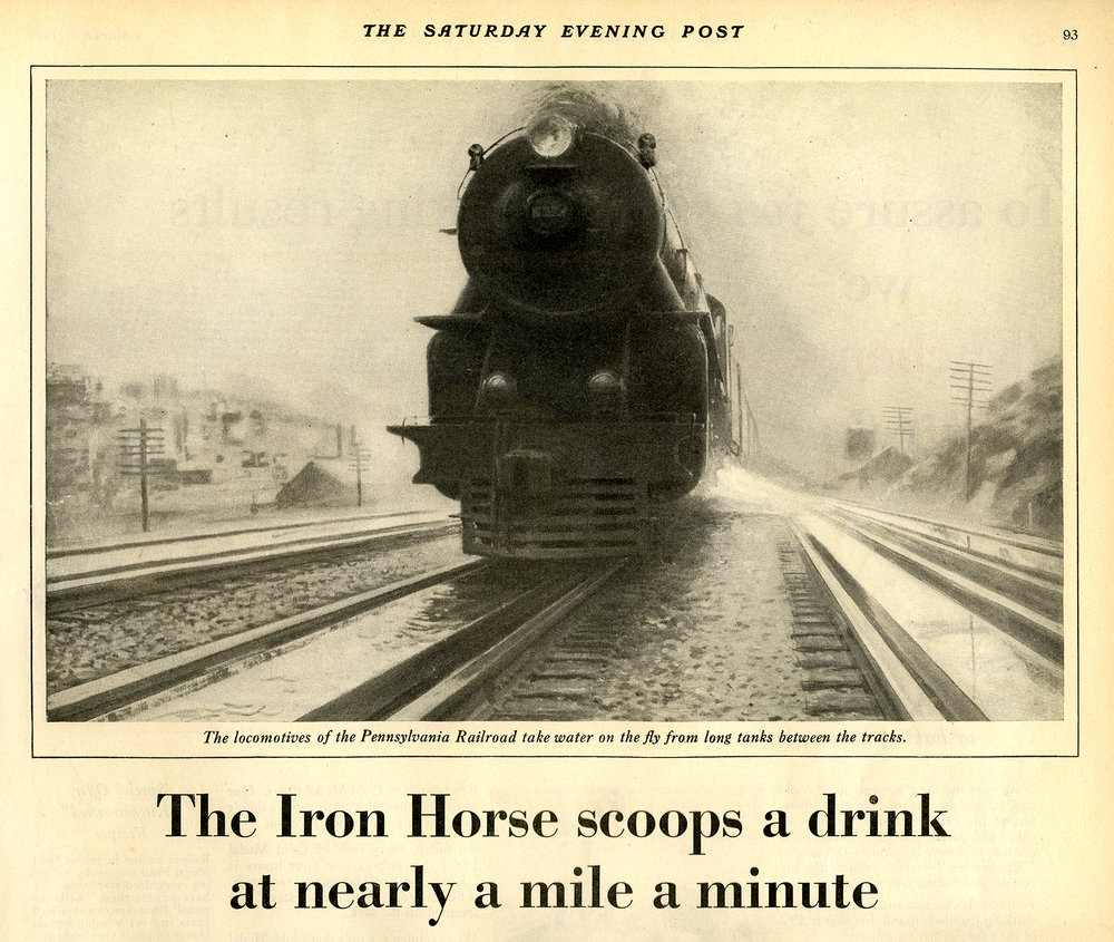 """Up ahead the trough appears, a long slender slot between the tracks, growing swiftly larger. In the cab, an alert hand tightens on a lever. The trough draws near more swiftly, rushes under the locomotive as though stung into a final burst of speed. The hand jerks sharply. Below, beneath the tender, the scoop darts down - plows a swishing furrow along the shallow trough. A rush of water funneled upward... a final speed driven spray as the tank in the tender overflows and the scoop springs back into place. The Iron Horse has had his drink...The Limited roars on its way unchecked.""  - Saturday Evening Post, 1928."