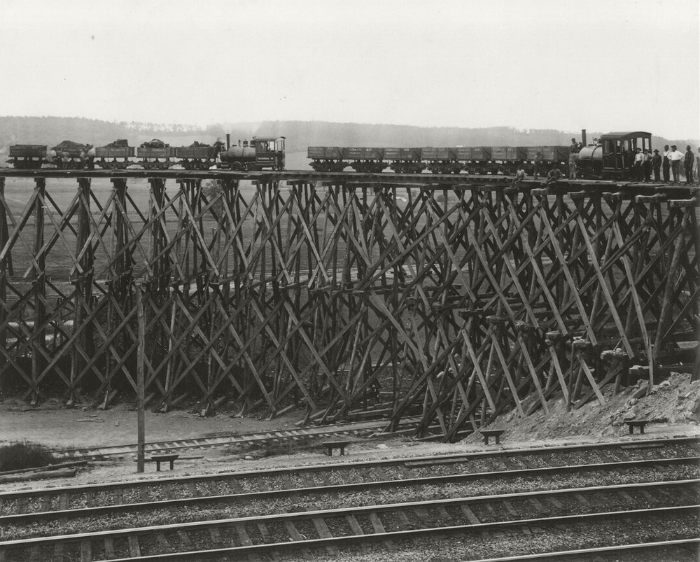 A temporary wooden trestle supports two diminutive 3-foot gauge steam locomotives and their hopper cars, used to haul fill material from land holdings along Zion Hill to the   six   mile   fill Charles A. Sims & Company constructed for the easternmost segment of the Atglen & Susquehanna Branch  .