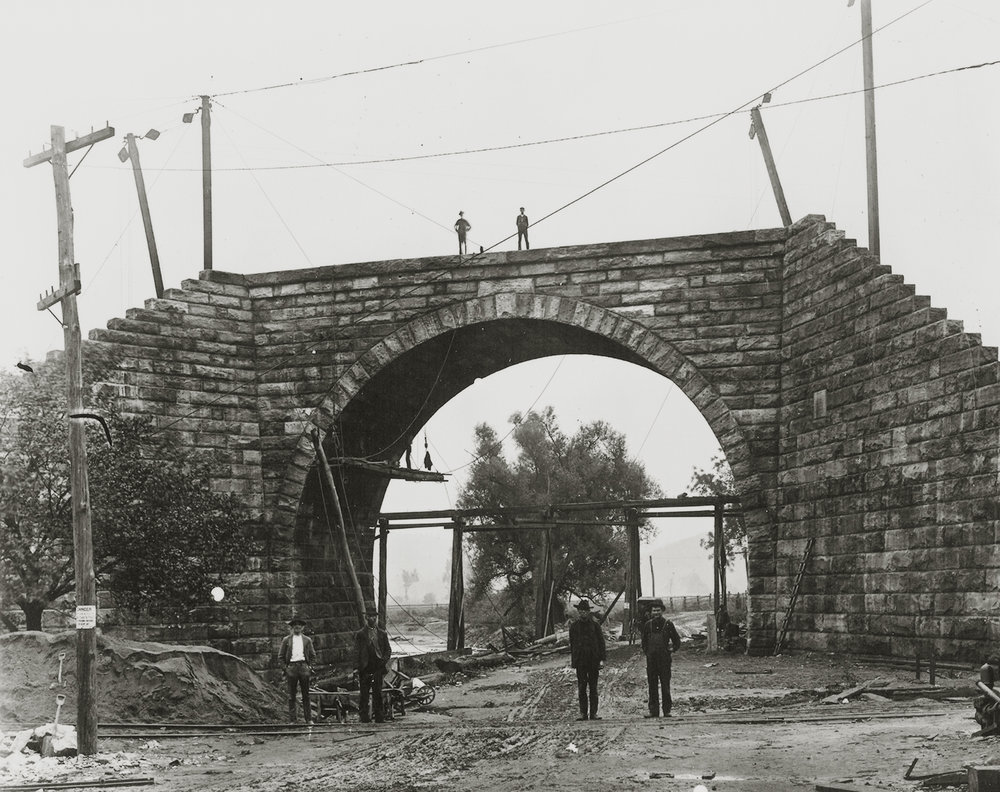 Workers pose in front of the masonry work of the 60' arch spanning Noble Road and the East Branch of the Octoraro Creek. While it appears that much of the stonework is complete, the task of backfilling the span and wing walls is yet to be completed as construction progresses west toward Mars Hill Summit.