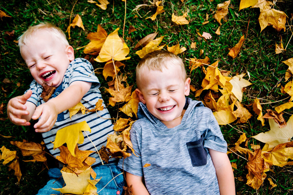 Brothers playing in autumn leaves