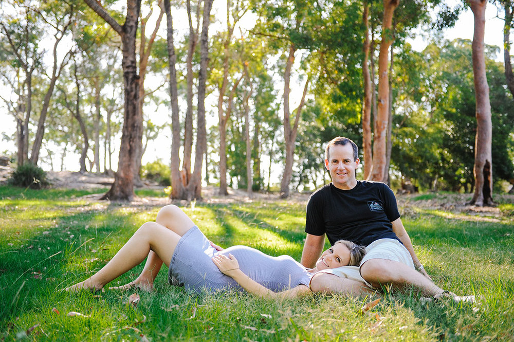 Pregnant wife lying in husband's lap in a green field