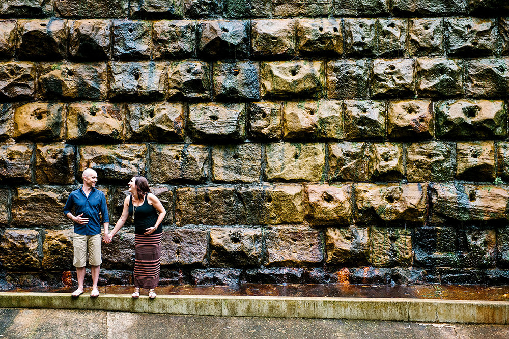 Pregnant couple laughing in front of textured stone wall