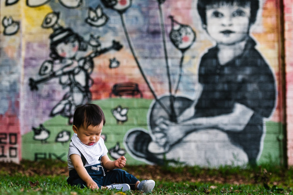 Graffiti wall behind baby boy