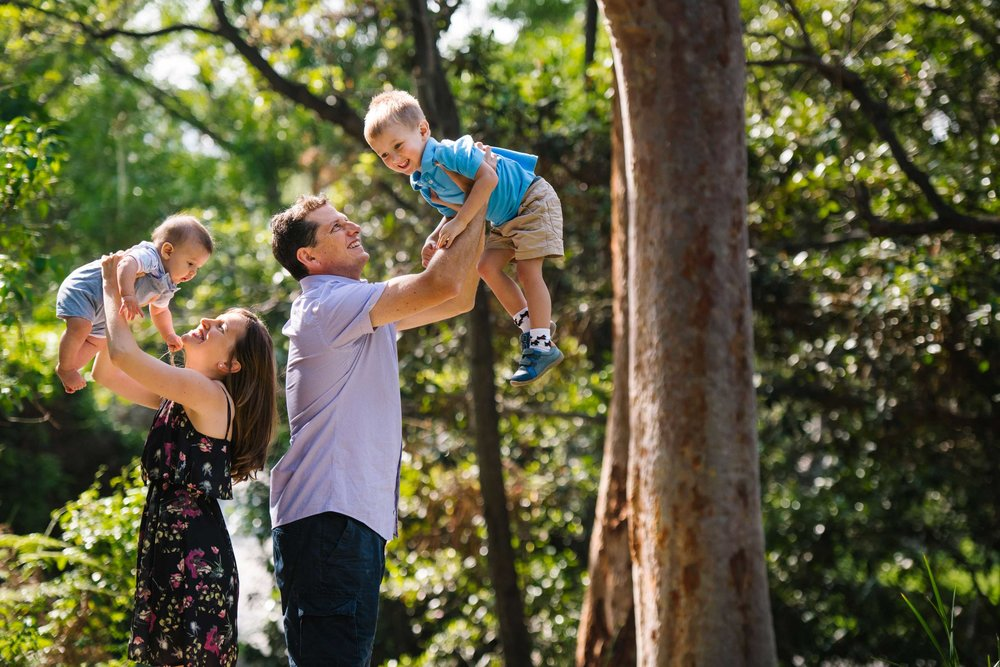 Parents hold their boys up in the air during family photo session