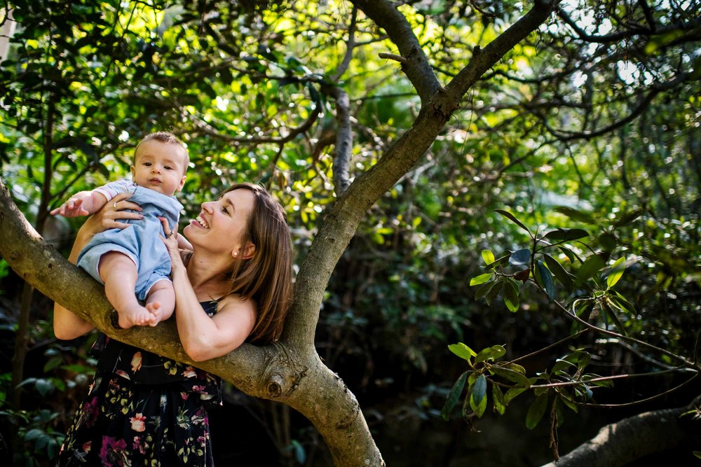 Mum holds her baby on the branch of a tree