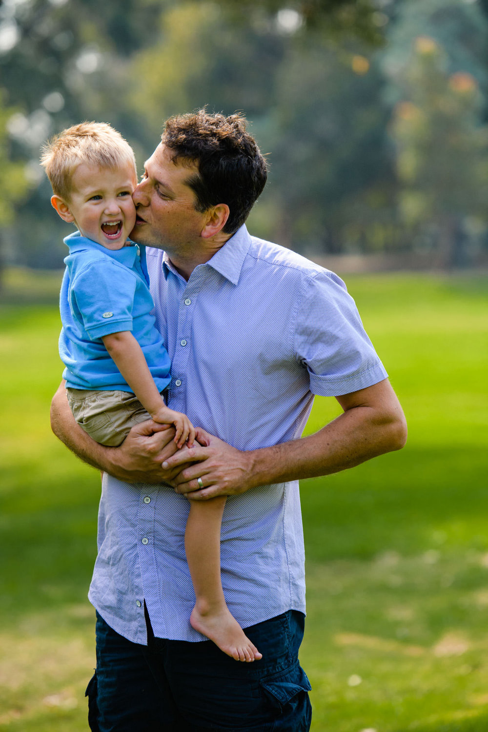 Toddler laughing as dad kisses him on the cheek