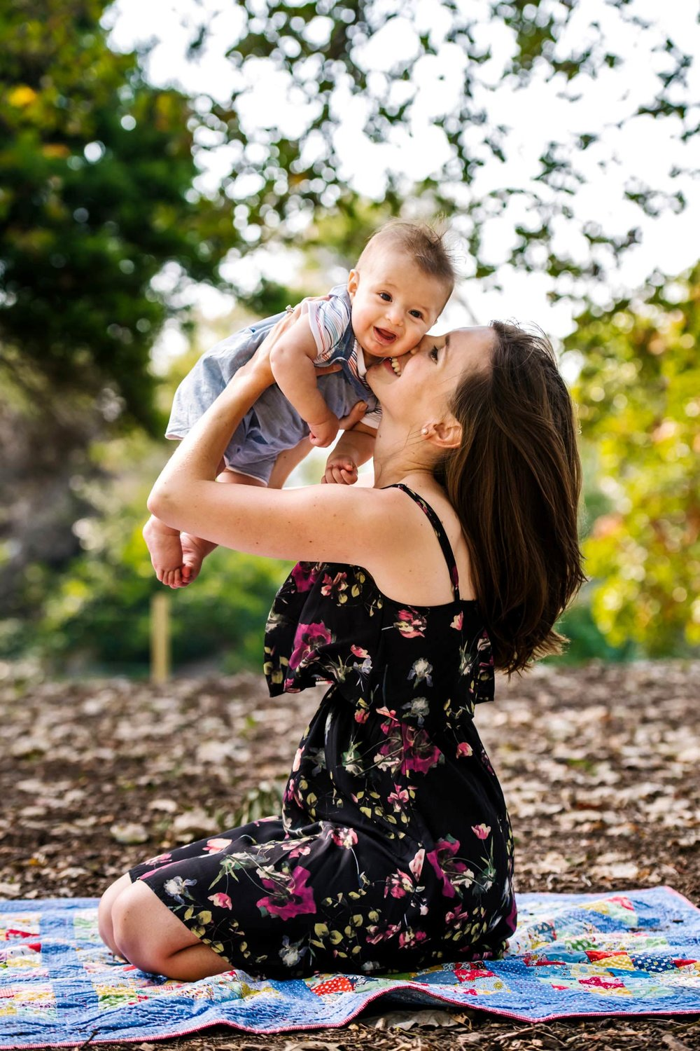 Mum kisses baby on the cheek during park photo session