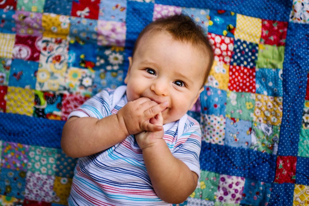 Baby boy smiling while lying on patchwork blanket