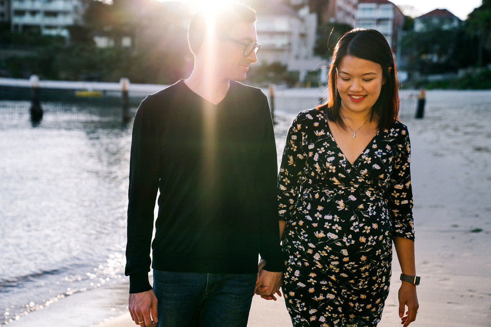 Couple walking up Little Manly Beach during maternity session