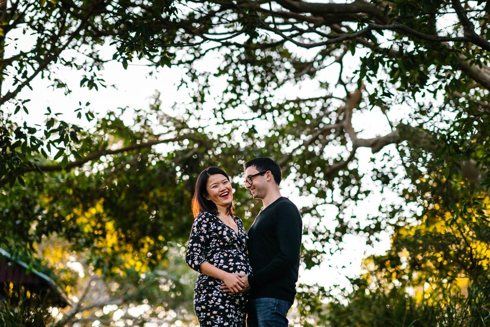 Pregnant couple laughing with trees in the background