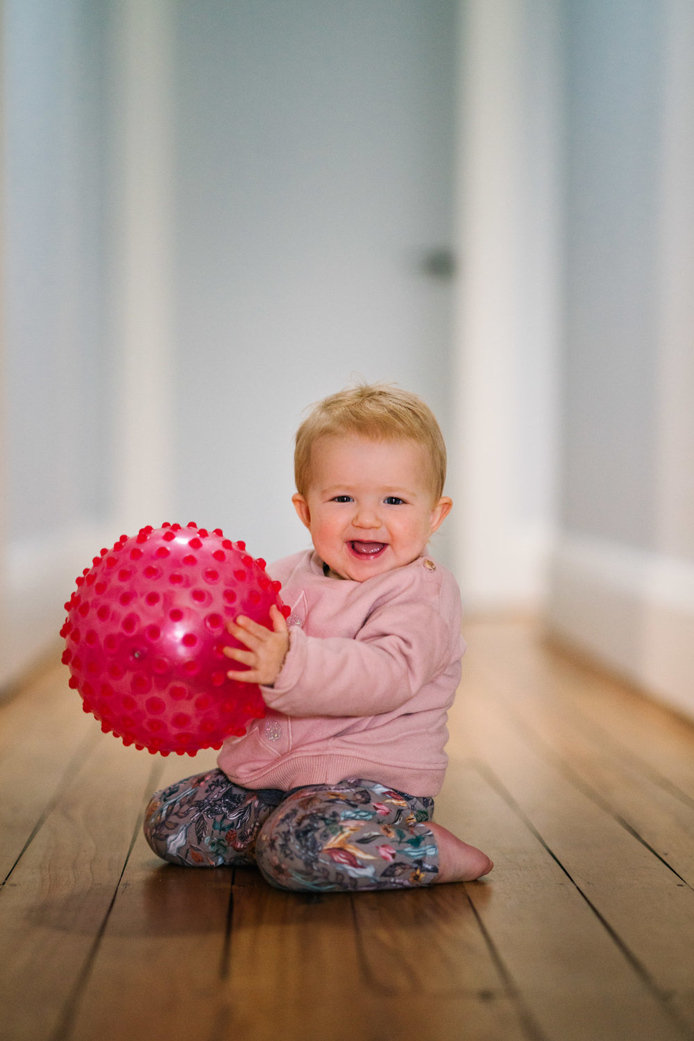 Baby playing with pink ball in period home in Coogee, NSW