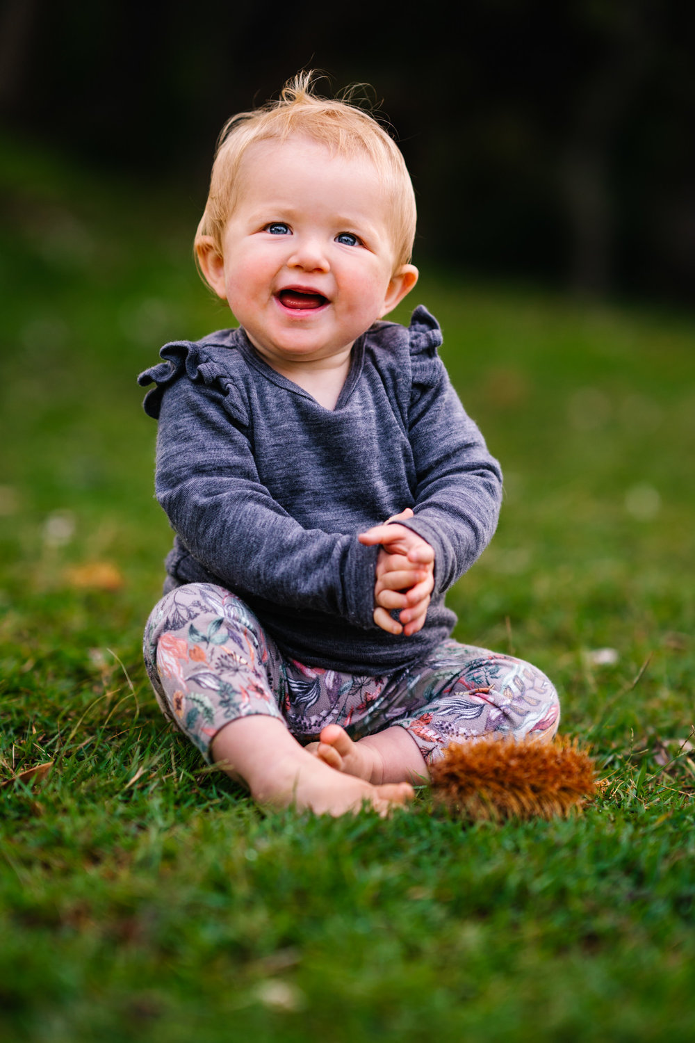 Baby girl smiling at the camera in a park