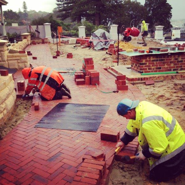 Header Course installation in Peppermint Grove. These recycled red bricks have been laid 'on-edge' and the header courses are being installed on a concrete bed to secure them in place and prevent movement over time.