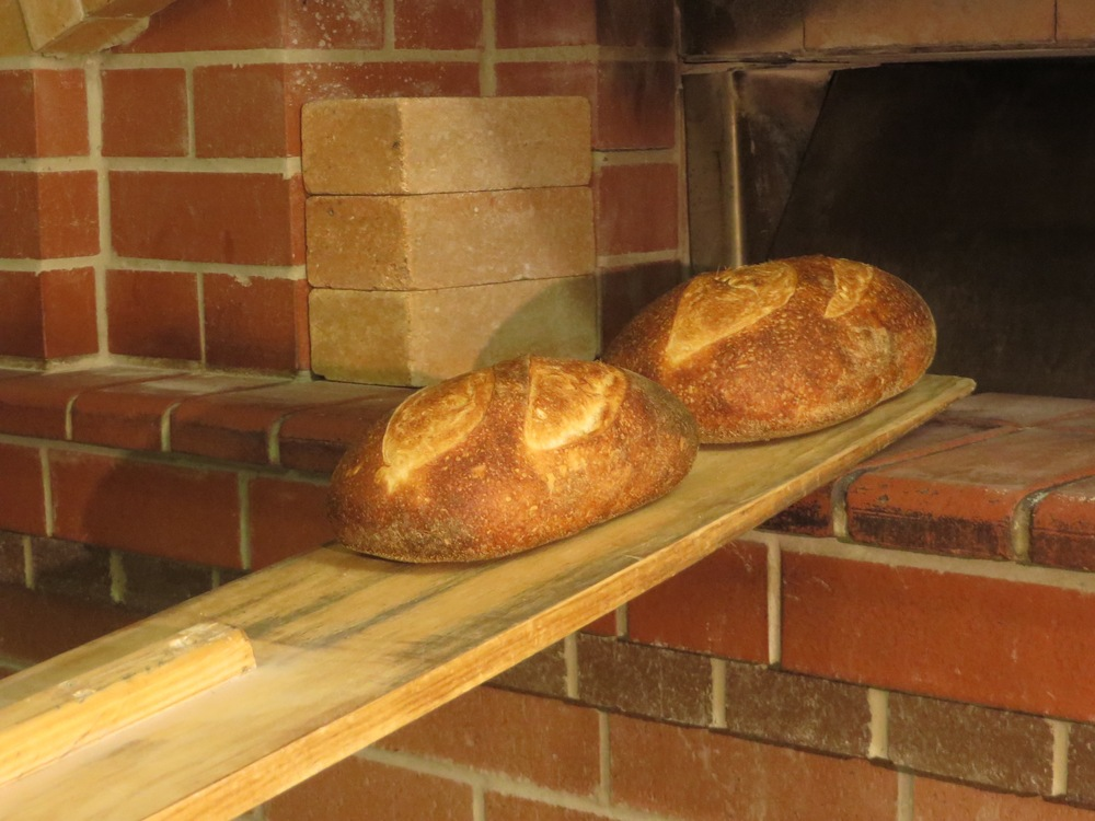 The oven is unloaded using the peel. The bread is then allowed to cool. The bake usually takes between 12 - 14 hours from the time the first doughs are made to the time the last loaf comes out of the oven. As a micro bakery, a single pair of hands is involved every step along the way. The baker that starts the bake finishes the bake.