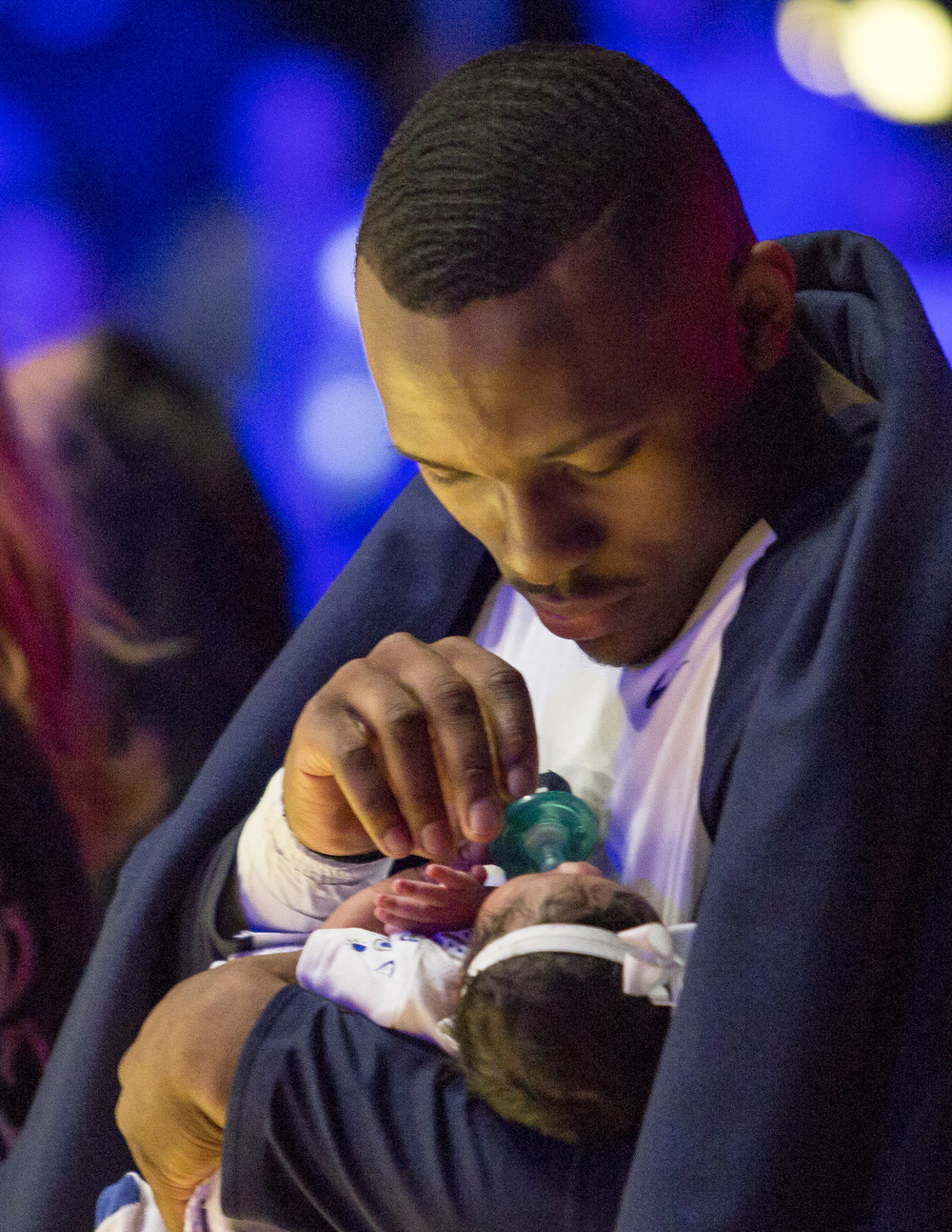 Senior guard Devin Foster holds his newborn daughter on the court of the Bryce Jordan Center during the senior day ceremony before the start of the game against Northwestern on Thursday, March 3, 2016.