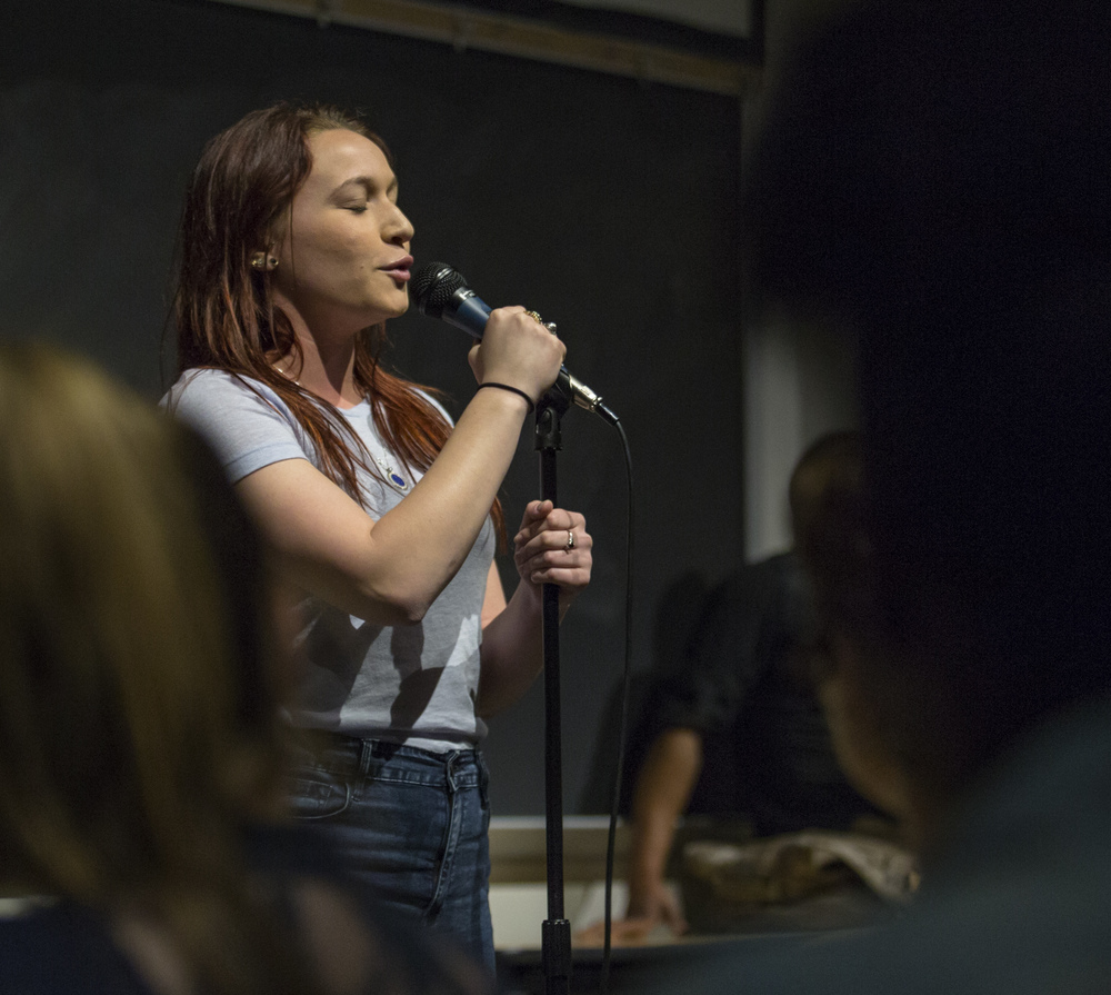 Carla Capone (sophomore - psychology) recites one of her poems during the open mic portion of the State Slam held in the Thomas Building on Thursday, March 24, 2016.