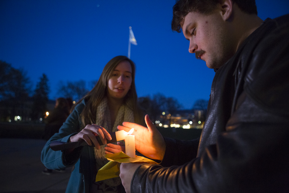 Sylvia Kitterman (senior - IST), left, lights a candle for Conner Mangan (senior - energy, business and finance) to begin the Candlelight Vigil Against Global Violence on the steps of Old Main on Tuesday, March 29, 2016.