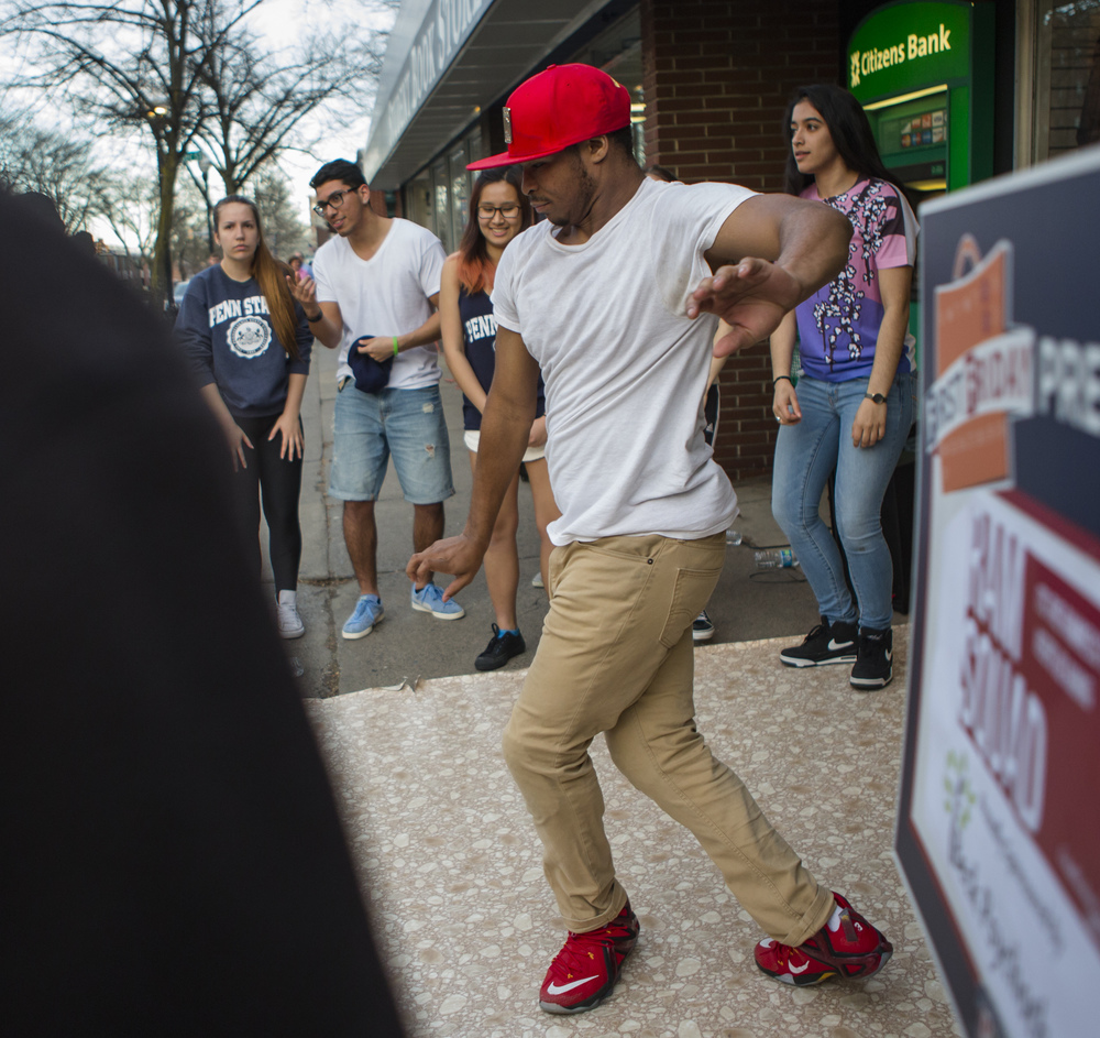 Quince Hutchings (freshman - DUS) dances with RAM Squad outside of the Student Book Store on College Ave. as part of First Friday in downtown State College on Friday, April 1, 2016.