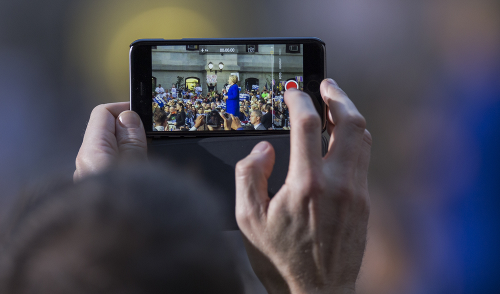 A supporter takes a video of Democratic presidential candidate Hillary Clinton on his phone as she speaks during her campaign rally held in the courtyard of City Hall in Philadelphia on Monday, April, 25, 2016.