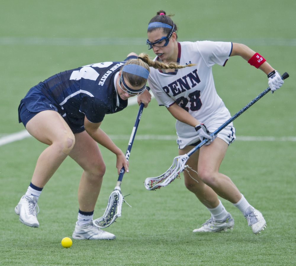 Penn State attacker Madison Carter scoops the ball under coverage from Penn mid-fielder Lely DeSimone during the NCAA quarterfinal game at the Penn State Lacrosse Stadium on Saturday, May 21, 2016.