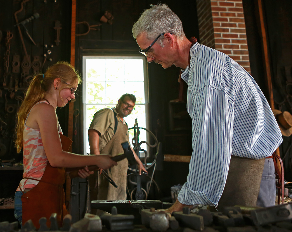 John Wood of Wilson NC, right, helps Mt. Nittany Middle School fifth grader Maeve Flanagan form the end of a fork as Eric Johnson stokes the furnace in the Boalsburg blacksmith shop during the Boalsburg Memorial Day festival on Monday, May 30, 2016.