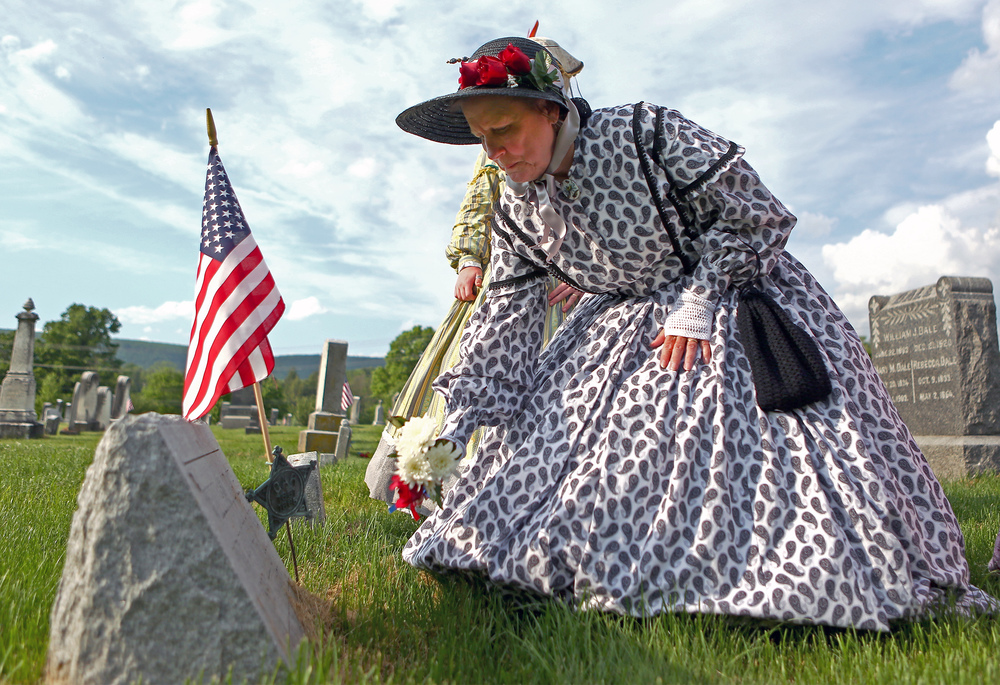 One of the Boalsburg Battery B ladies May Fisher places a bouquet of flowers at the headstone of a veteran in the Zion Evangelical Lutheran Church as part of the Boalsburg Memorial Day ceremony on Monday, May 30, 2016.