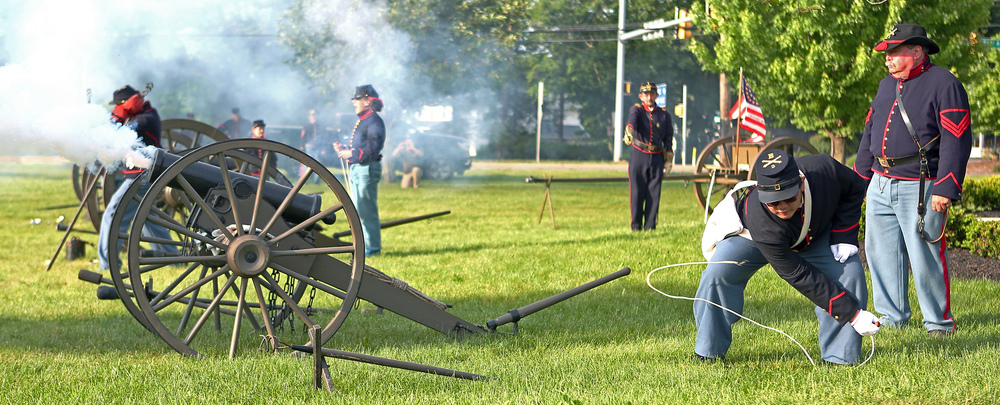 Kit Lang of Williamsport fires one of the Boalsburg Battery B canons to conclude the Memorial Day ceremony in front of the Zion Evangelical Lutheran Church on Monday, May 30, 2016.