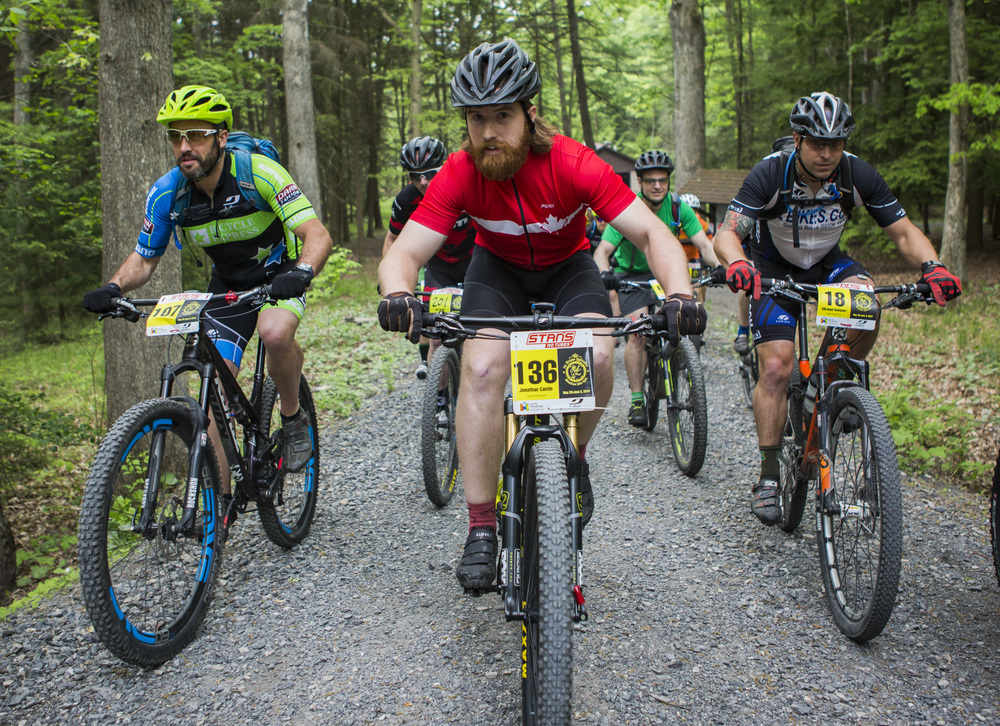 Jonathan Cantin pedals up the path from the starting line of the fourth stage of the Tran-Sylvania Epic Mountain Bike Ride in the main parking lot of R.B. Winter State Park surrounded by other riders on Thursday, June 2, 2016