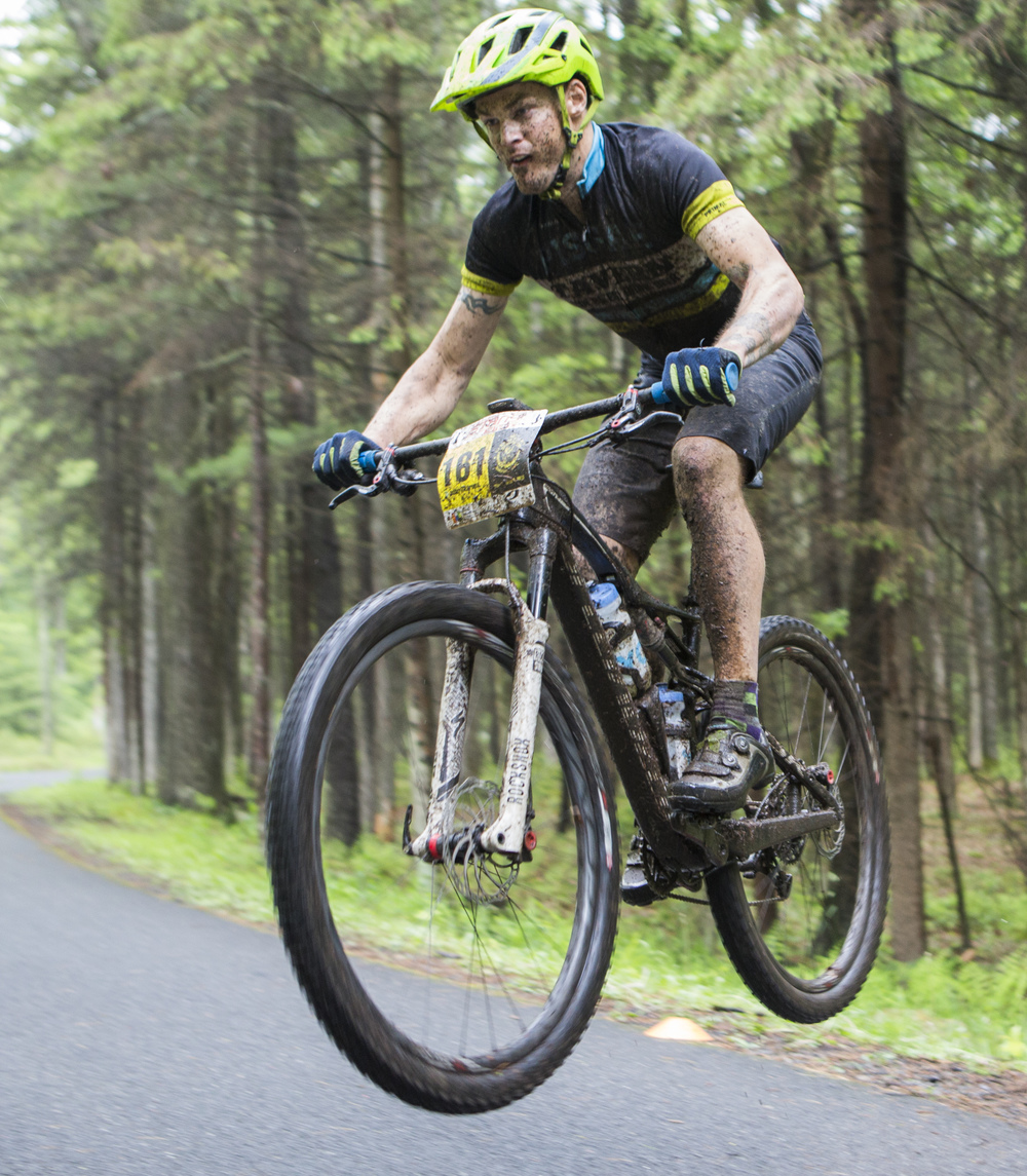 John Skarupa of the Cage Rage team catches some air on the road jump as part of the fifth enduro section of the fourth stage of the Tran-Sylvania Epic Mountain Bike Ride on Thursday, June 2, 2016.