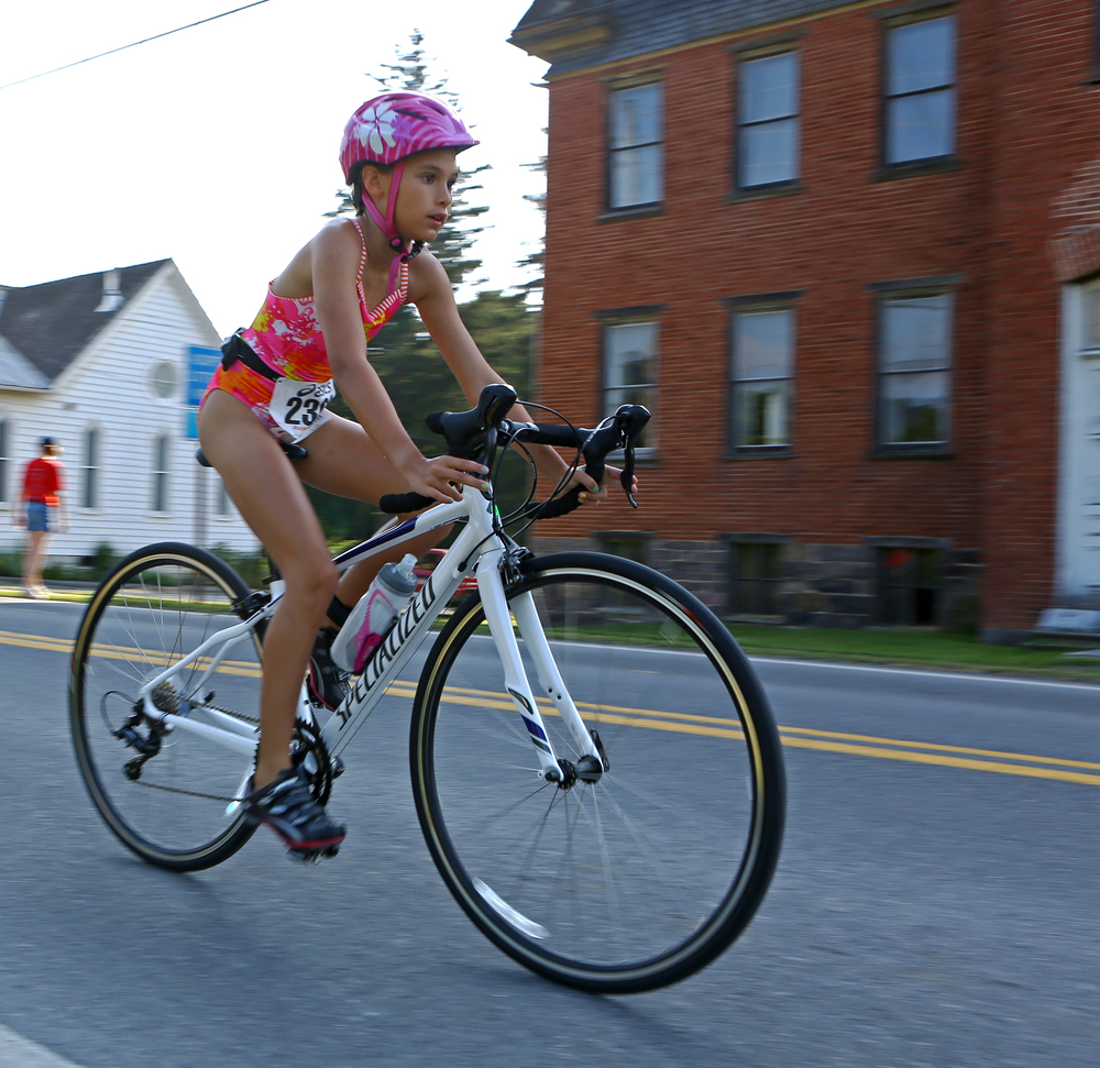Marlee Kwasnica of State College pedals down North Street in Millheim during the cycling portion of the Millheim Pool Spring Triathlon on Saturday, June 25, 2016.