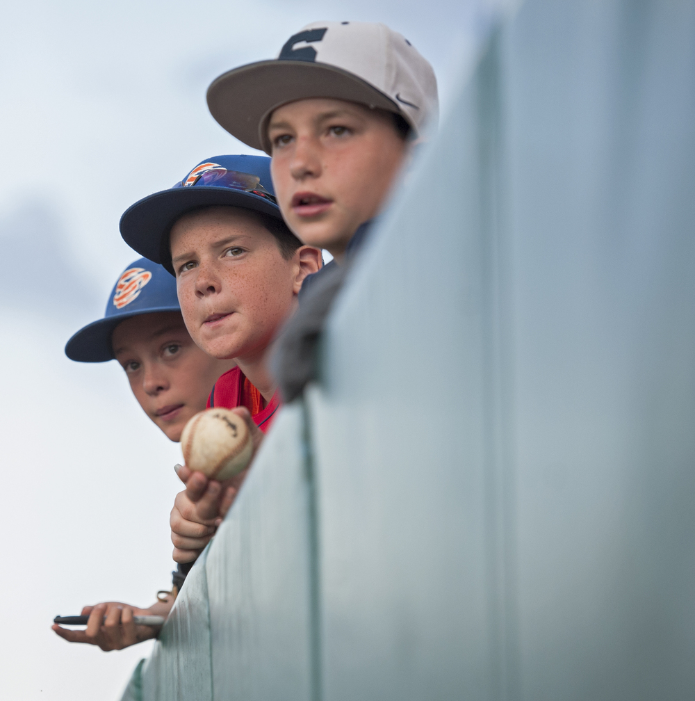 Three young fans lean over the wall of Medlar Field waiting to catch State College Spikes players to autograph their baseballs and posters before the start of the game against the Mahoning Valley Shredders on Friday, July 1, 2016.