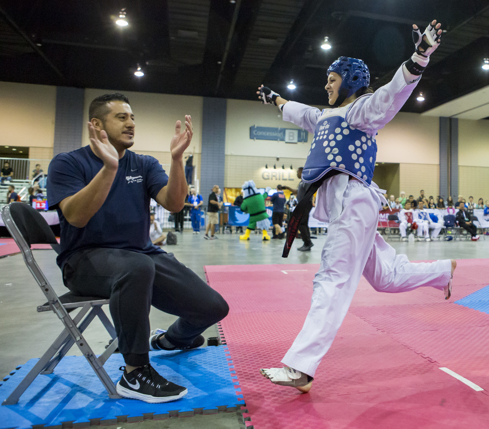 Alexandra Lopez and her coach celebrate after winning a final sparring match in the USA Taekwondo National Championships held at the Greater Richmond Convention Center in Richmond, Va. on Thursday, July 7, 2016.