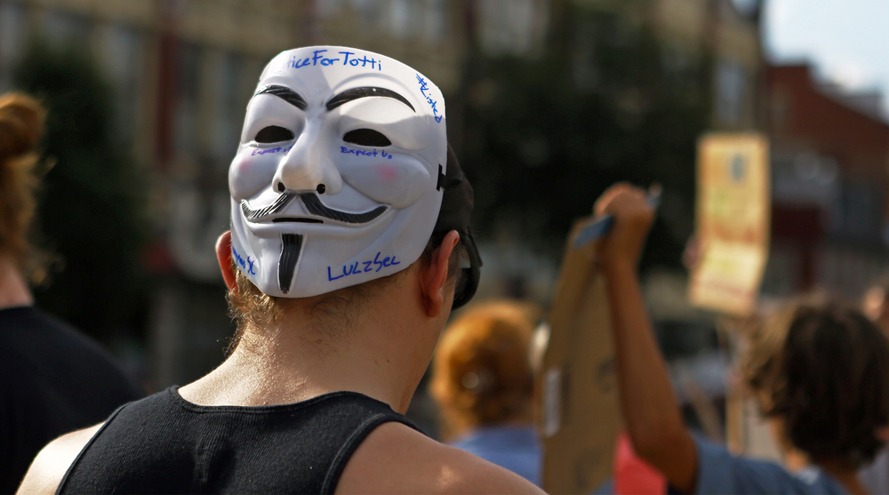 """Justin Wian of Bellefonte wears a Guy Faux mask on the back of his head reading """"Justice for Totti"""" as he joins the other Centre County residents in front of the Centre County courthouse on Monday, July 18, 2016 calling for justice for Totti, a Department of Corrections drug detection dog that died of heat exposure after being locked in a squad car for over two hours."""