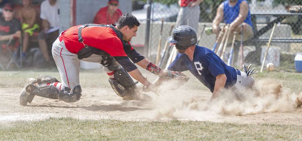 Howard Hawks catcher Evan Gettig reaches out to tag Phillipsburg center fielder Brandon Quay as he slides safely into home base during the Centre County League game at Howard Elementary School on Sunday, July 24, 2016.