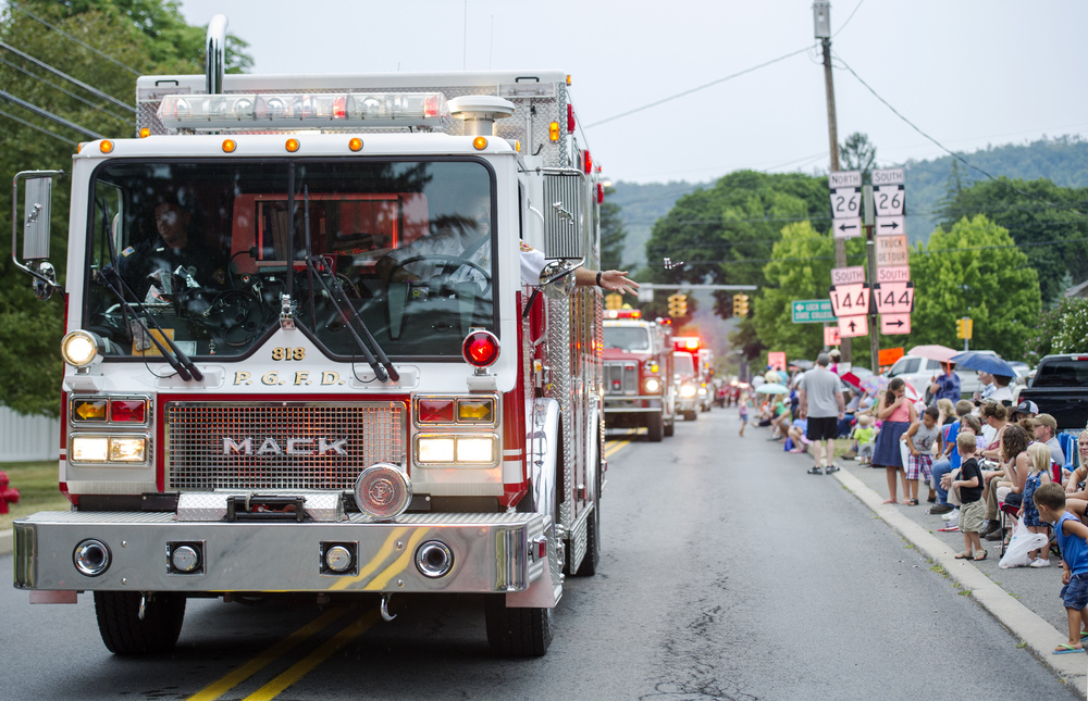 Members of the Pleasant Gap Fire Company throw Tootsie Rolls from their fire engine during the company's annual parade through Pleasant Gap on Thursday, July 28, 2016.