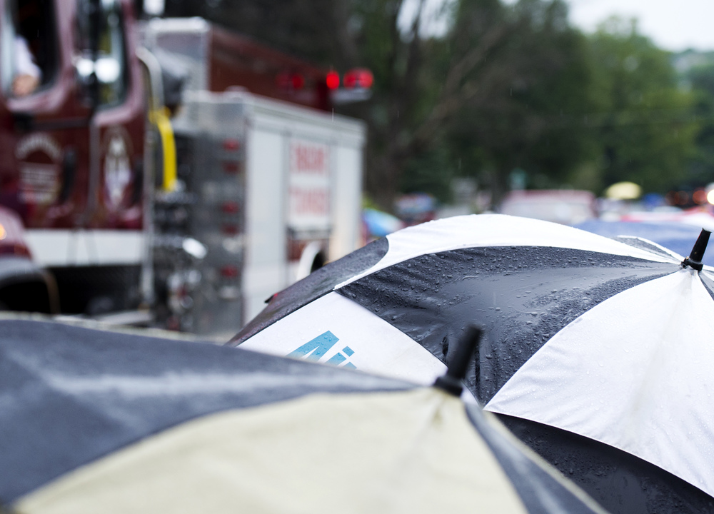 Attendees of the Pleasant Gap Fire Company's annual parade use umbrellas to cover from the steady drizzle soaking the parade on Thursday, July 28, 2016.