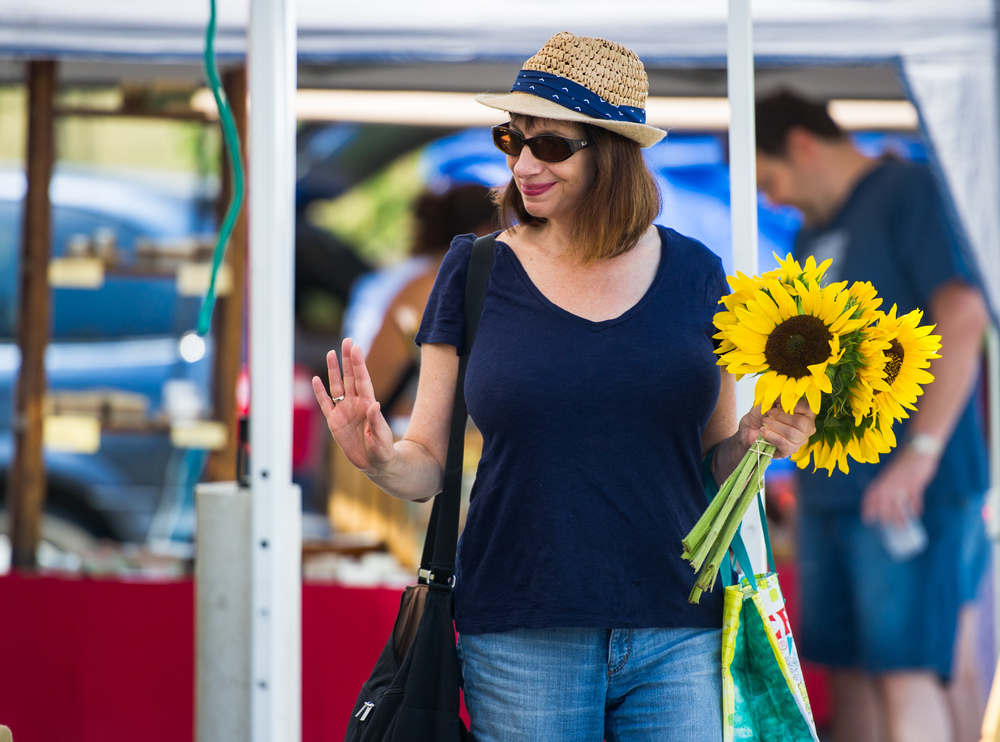 Willa Silverman of State College waves to one of the vendors while attending the North Atherton Farmer's Market held in the parking lot of Home Depot on Saturday, Aug. 6, 2016.