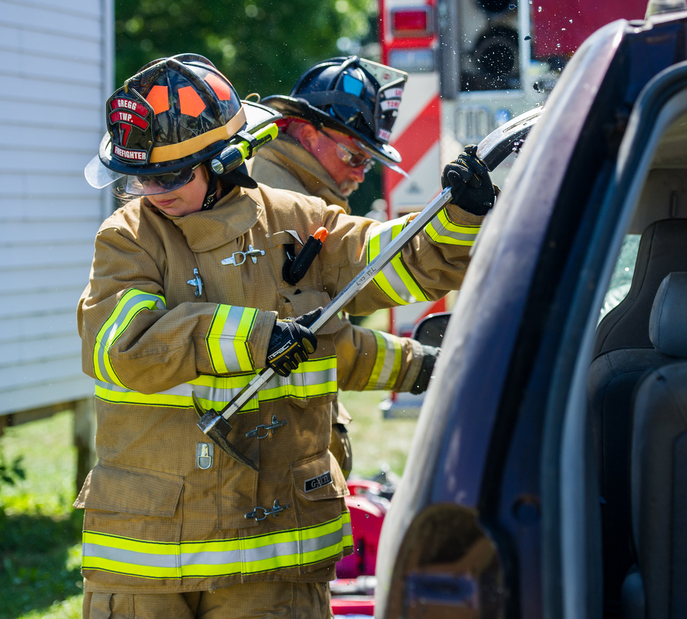 Kammy Young scrapes glass chips from a van as the Gregg Township Fire Company demonstrates their vehicle rescue techniques and newly acquired tools during the Gregg Township Fire Company safety awareness event at the company's carnival grounds in Spring Mills on Saturday, Aug. 6, 2016.
