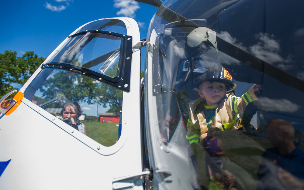 Kamerzyn Holt, 2, examines the controls of the Life Flight helicopter during the Gregg Township Fire Company safety awareness event held at the company's carnival grounds in Spring Mills on Saturday, Aug. 6, 2016.