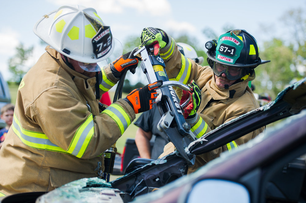 Gregg Township Fire Company assistant chief Brandon Young, left, helps captain Dale Tischer use the hydraulic cutters to cut the a-pillar from a van as the company demonstrates their vehicle rescue techniques at the Gregg Township Fire Company safety awareness event at the company's carnival grounds on Saturday, Aug. 6, 2016.